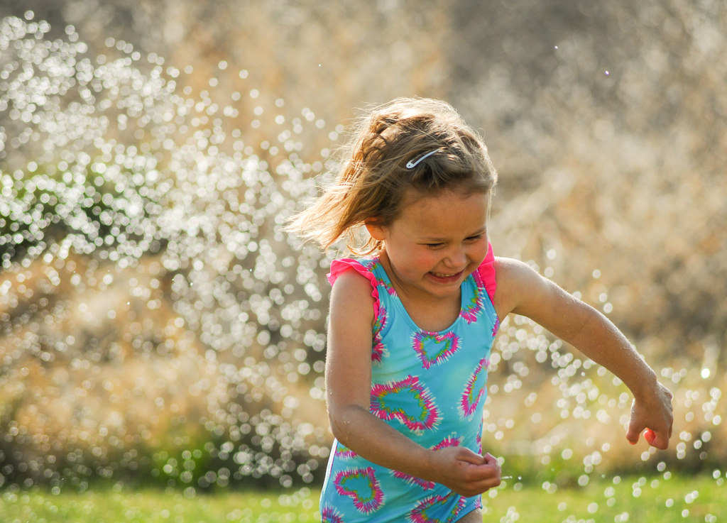 Child Playing in Sprinkler in Front Yard
