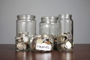 "coin saving jars with text displaying ""travel"""