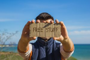 "man holding up cardboard sign that reads ""free stuff"""