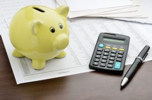 piggy bank with calculator and financial paperwork budgeting