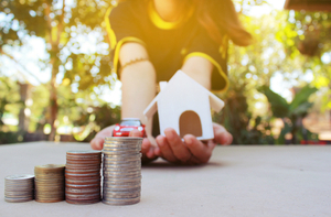Concept of home buying and money illustrated by stacked coins and woman holding model house