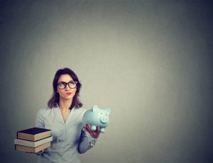young woman holding books and piggy bank representing education and debt, respectively.