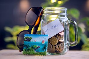 Holiday and vacation budget jar alongside sunglasses and a tropical picture