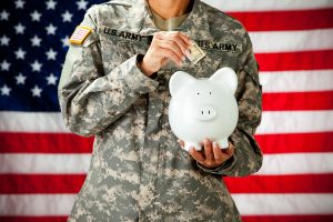 Military Female Putting Money In Piggy Bank