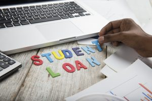 "Hands spelling out ""Student Loan"" with colorful letters on desk laptop and papers."