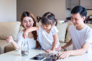 Parents teaching young daughter about money