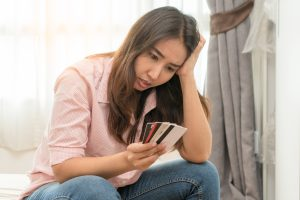 Young woman stressed by credit card debt