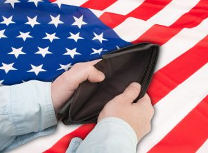 Hands opening empty wallet in front of American flag.