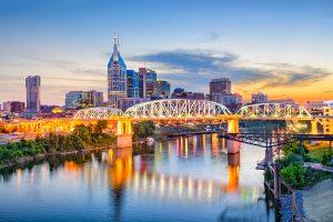 Downtown Nashville skyline at dusk. A pedestrian bridge crosses the Cumberland River.