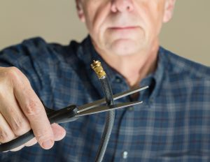 Older man holding coaxial cable between scissors