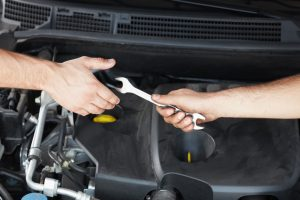 male hand offering wrench to hand of a friend under the hood of a car