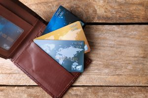 leather wallet displaying multiple credit cards on wooden background