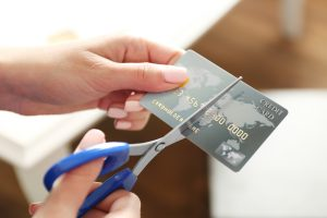 image of female hands holding scissors to cut credit card