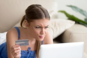 woman holding credit card and looking at laptop