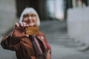 Older woman holding up credit card on bank steps