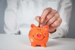 Orange piggy bank with man putting coin inside