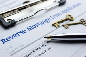 Close up of reverse mortgage loan application with pen and two brass keys.