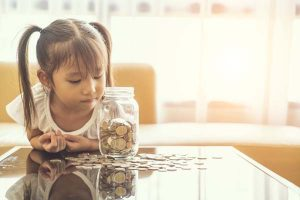Little girl looking at clear glass jar filled with coins.