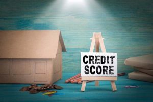 """Cardboard replica of house, books, pens, and coins sit behind an easel that reads """"credit score""""."""