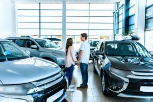 Man and woman holding hands standing in showroom of car dealership.