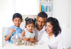 Family of four sits on couch counting change saved in a large glass jar.