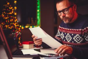 man at table concentrating on financial paperwork. Christmas decorations in background.