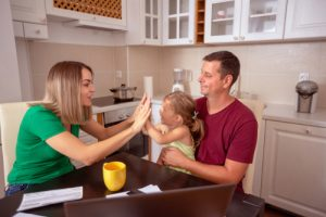 young family in kitchen at table with toddler daughter and some financial paperwork