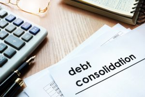 """Desk with pens, calculator, glasses, notebook, and papers with the words """"Debt Consolidation"""""""