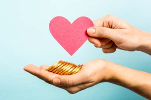 Hands holding a paper heart and gold-colored coins