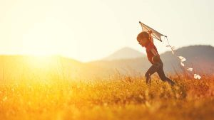 happy child with a kite running on meadow in summer in nature