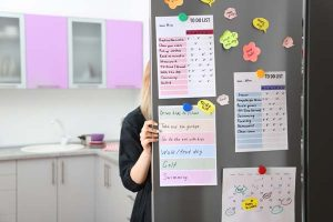 Stainless steel refrigerator door with lists and schedules attached with magnets. Woman standing on other side looking into refrigerator.