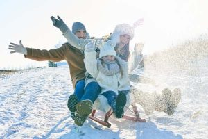 Family driving sled on snow having fun in winter