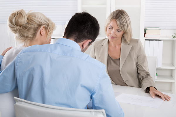 family consulting with financial advisor at desk