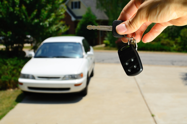 hand holding keys with used car in background, out of focus