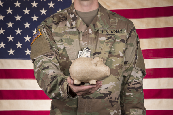 uniformed military service member holding piggy bank in front of American flag